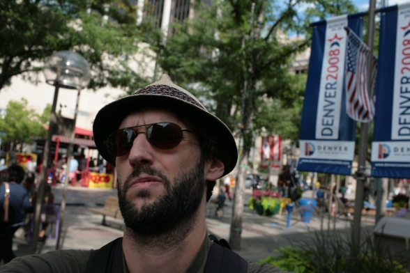 This is Matthias G. Bernold in 16th Street Mall in Denver, CO. Because of his grim expression, his dark shades and facial hair he could be easily mistaken for a violent protester. But he is not.